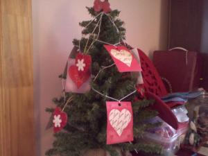A mini-Christmas tree decorated with paper hearts cut from a gift bag.