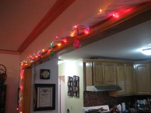 A white gauze babywearing wrap used as a garland for colored Christmas lights with a white cord.