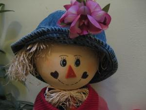 Our scarecrow Rosie, gets a new hat and flower.